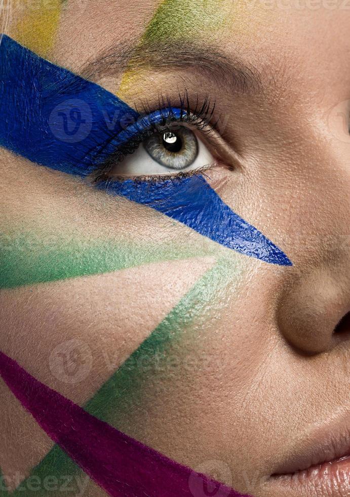 Close up del volto di donna con il trucco multicolor foto