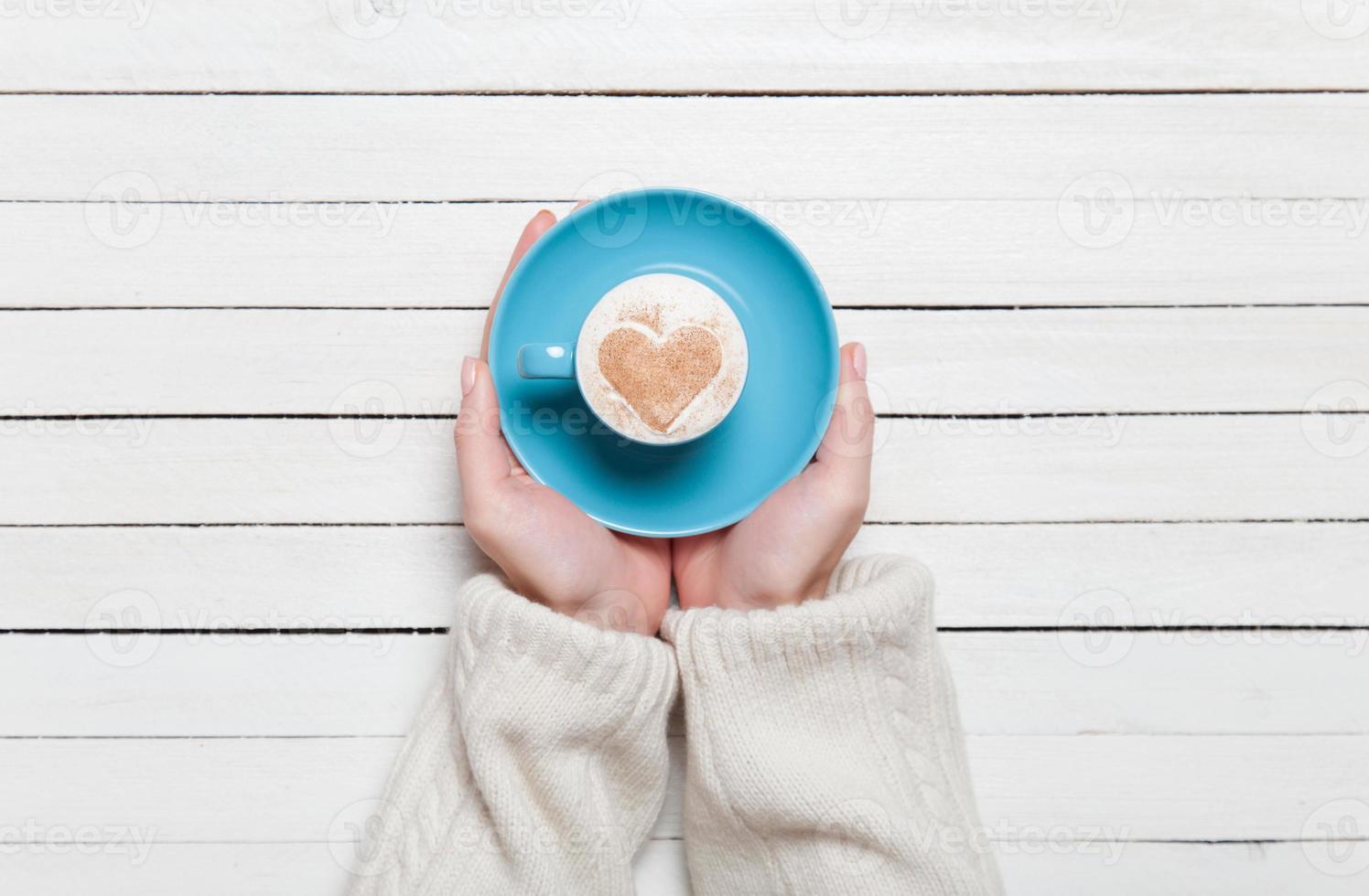 mani femminili che tengono tazza di caffè sul tavolo di legno. foto