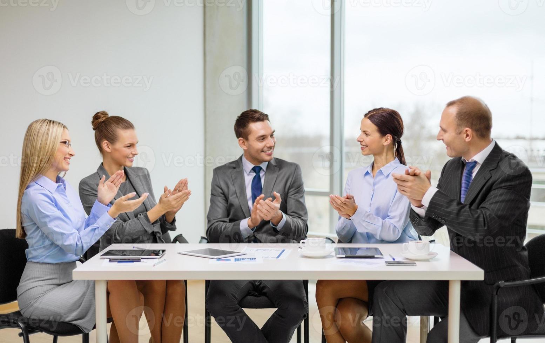 squadra di affari con le mani d'applauso del computer portatile foto