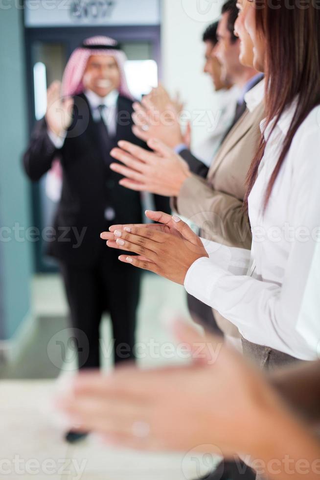 squadra di affari che applaude per accogliere l'uomo d'affari arabo foto