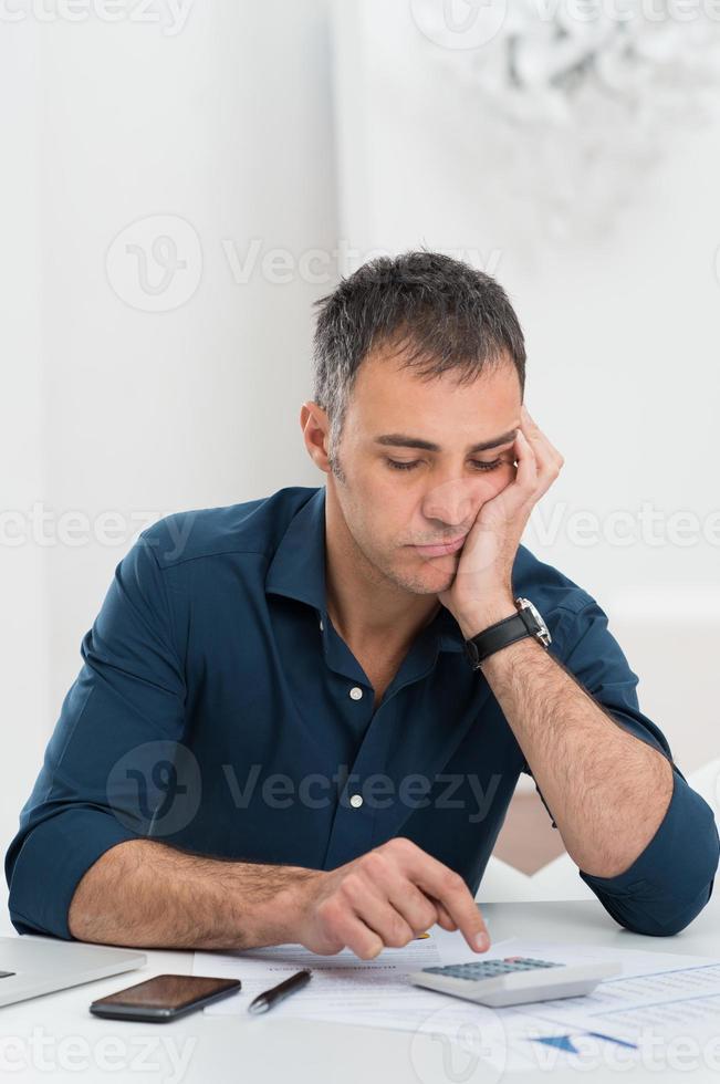 uomo stanco che fa i calcoli foto