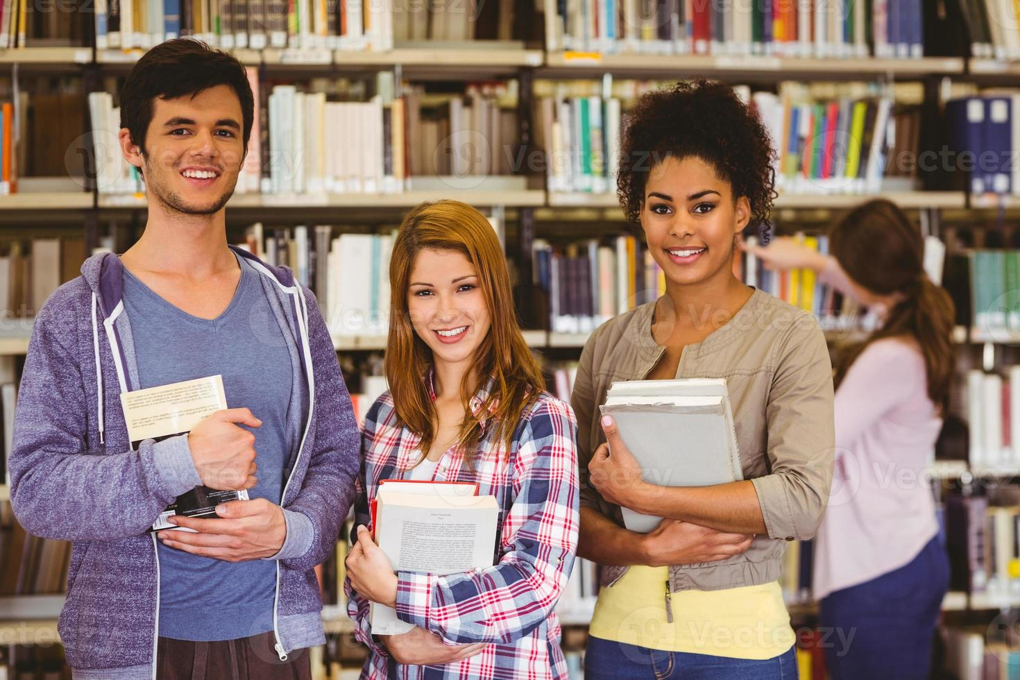 studenti in piedi e sorridenti a libri con fotocamera foto
