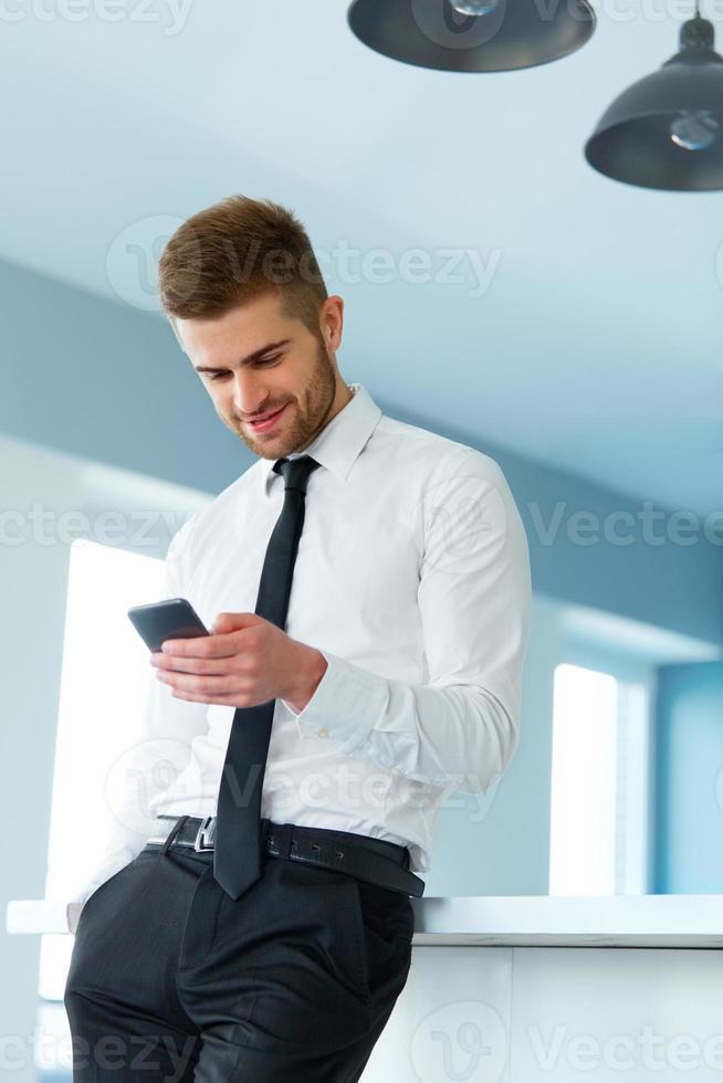 uomo d'affari leggendo qualcosa sullo schermo del telefono cellulare foto