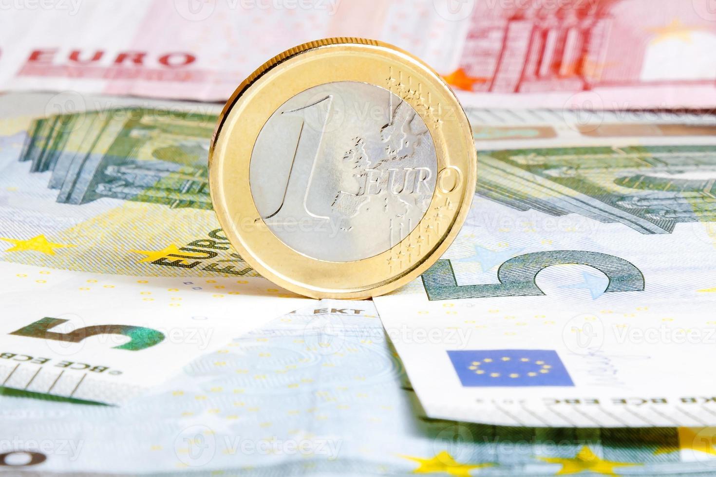 una moneta da un euro sulle banconote foto