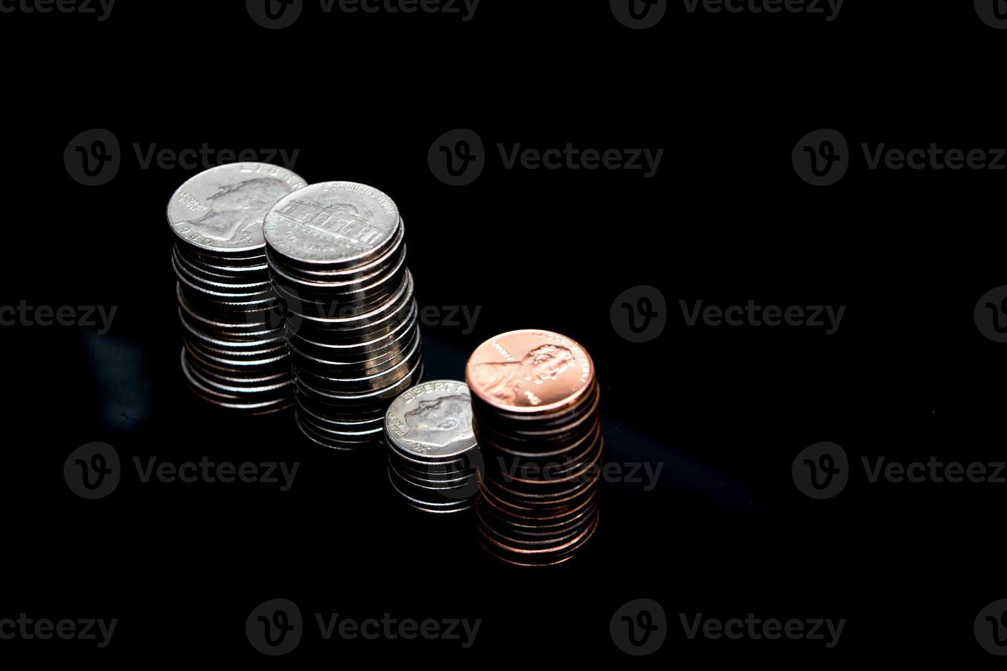 pila di monete sulla superficie nera foto