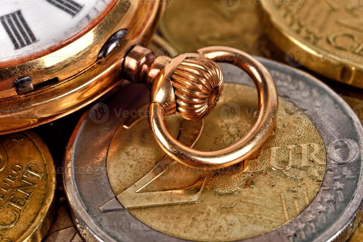 monete in euro e orologio da tasca foto
