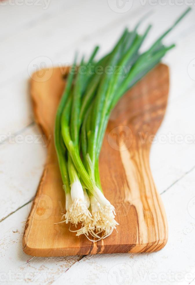 fattoria sollevato cipolle verdi organiche su fondo in legno foto