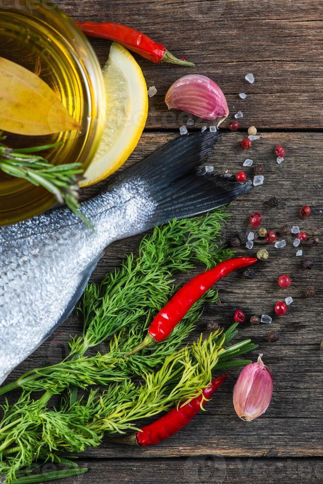 pesce fresco di mare intero con erbe aromatiche e spezie foto