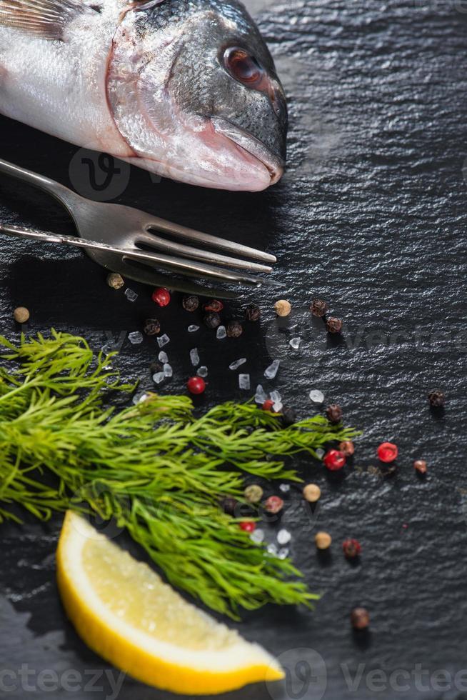 pesce di mare intero fresco con erbe aromatiche, concetto di cottura foto