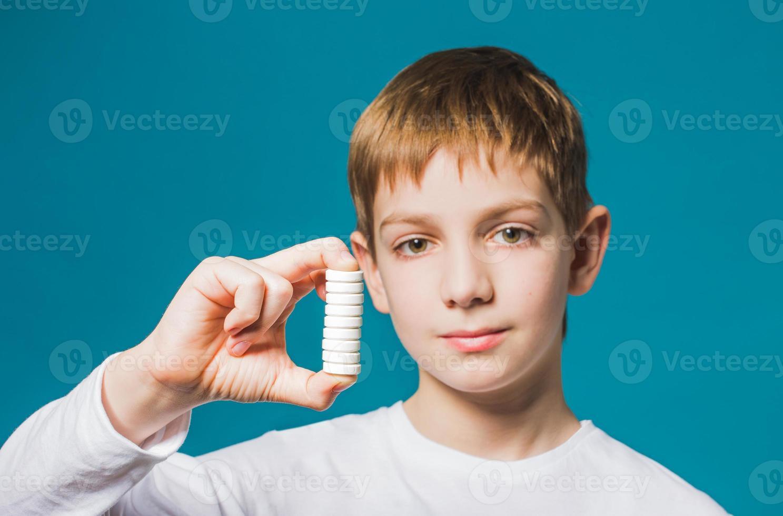 vicino ritratto di un ragazzo in possesso di pillole foto