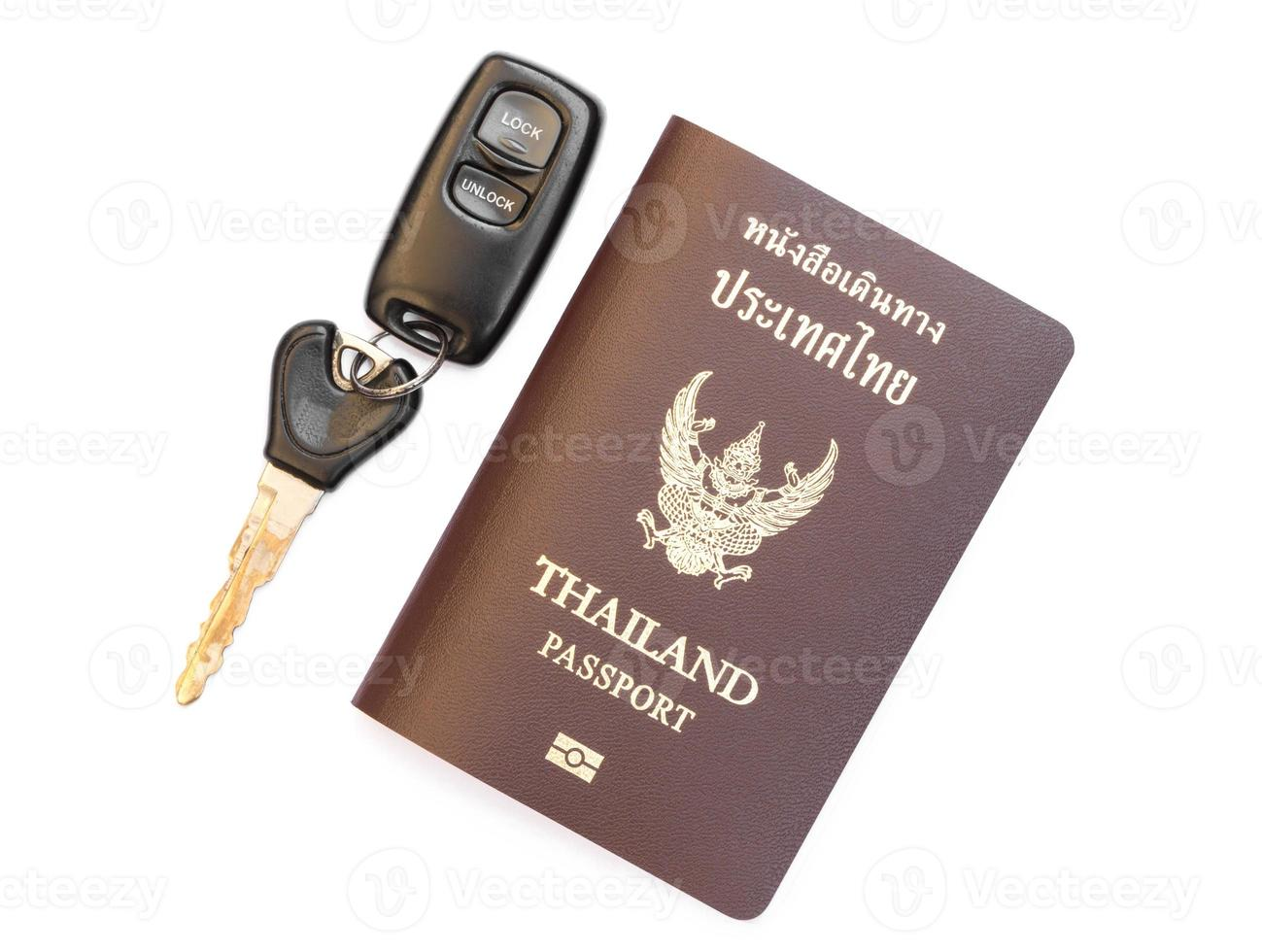 passaporto della Tailandia con la chiave dell'automobile su bianco foto