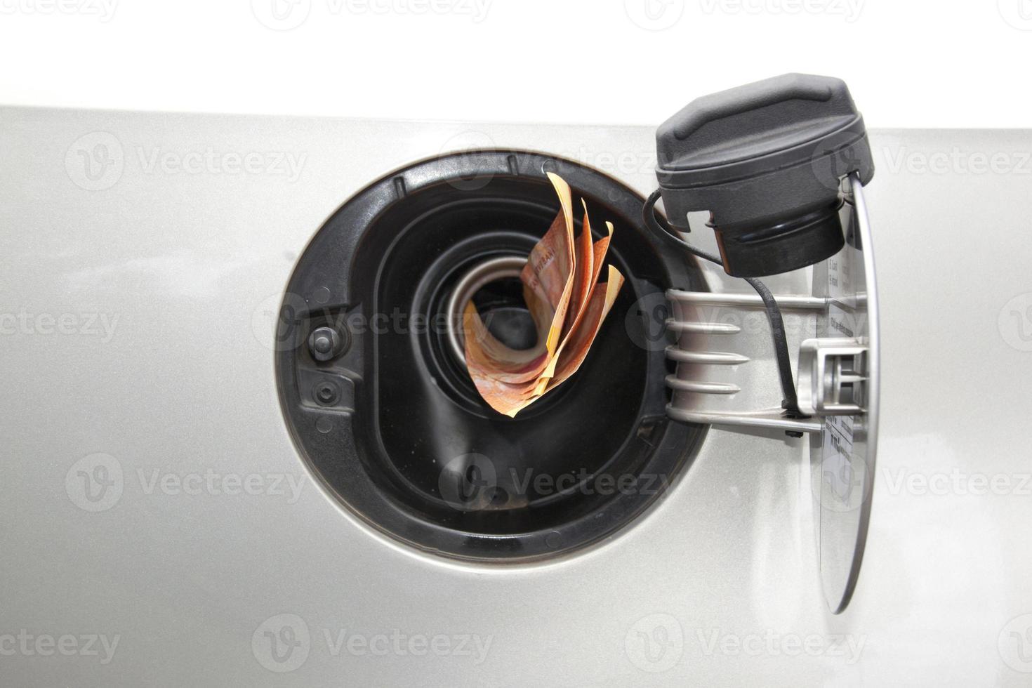 banconote di concetto che si alimentano nel tubo del refil della benzina foto