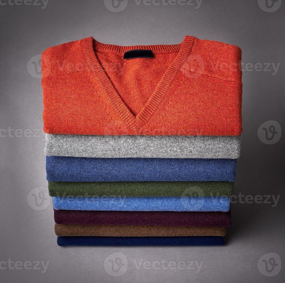 pila di maglione su una terra posteriore grigia foto