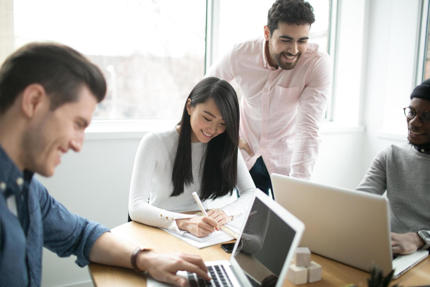 giovani professionisti che lavorano su computer portatili in un ufficio foto