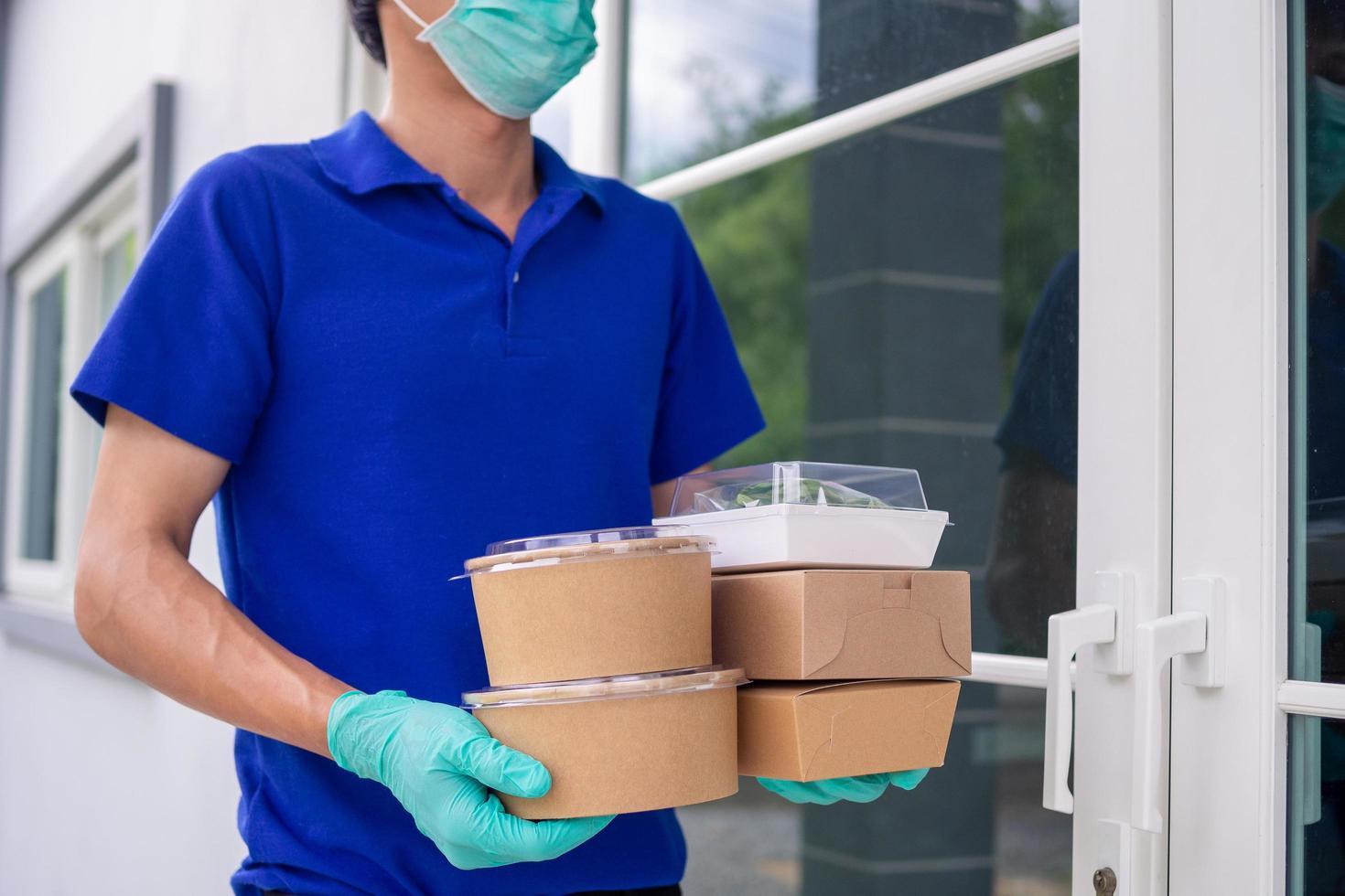 un addetto alla consegna di alimenti vestito con indumenti protettivi consegna il pranzo al cliente foto