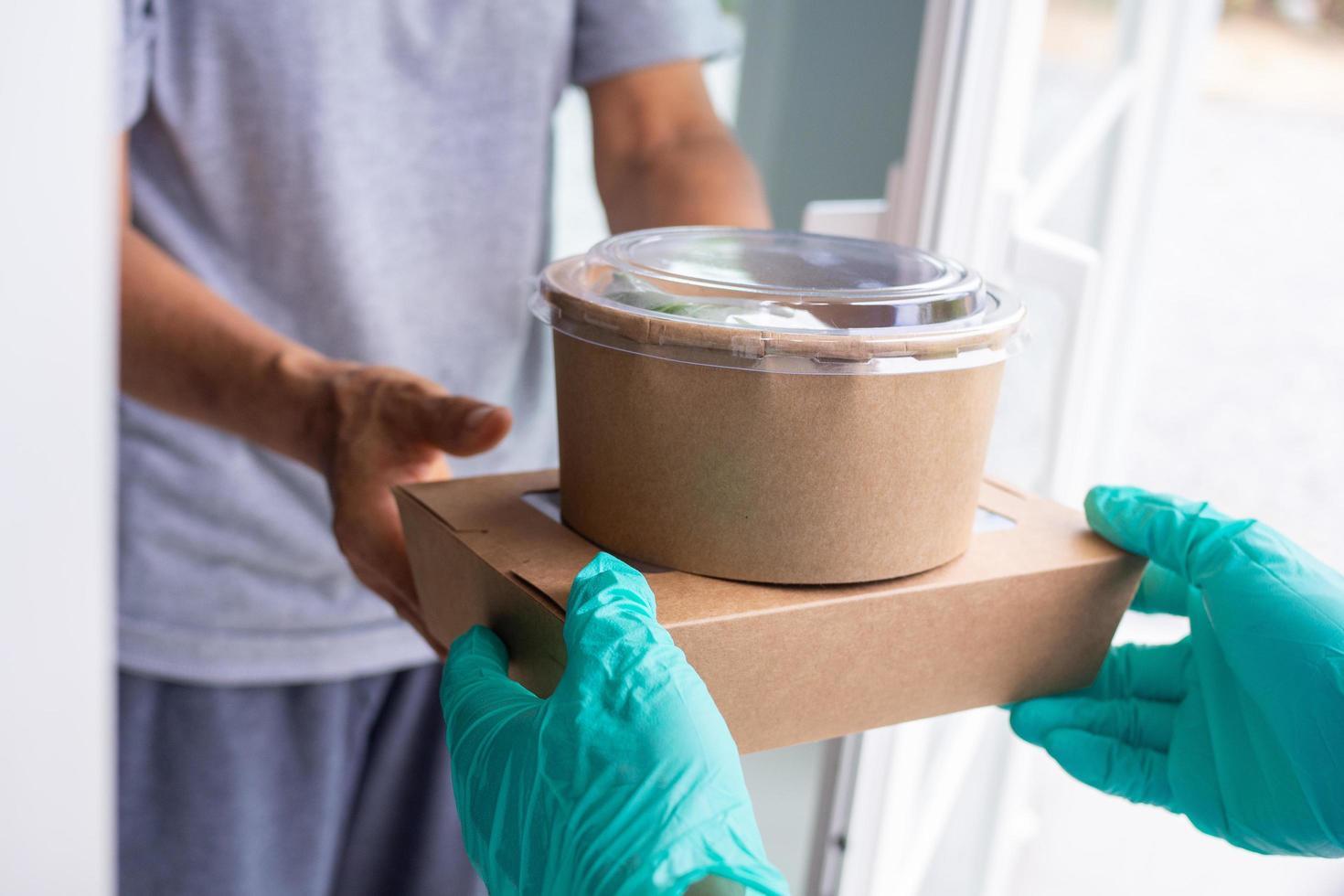 L'addetto alla consegna degli alimenti incontra il cliente alla porta con cibo da asporto foto