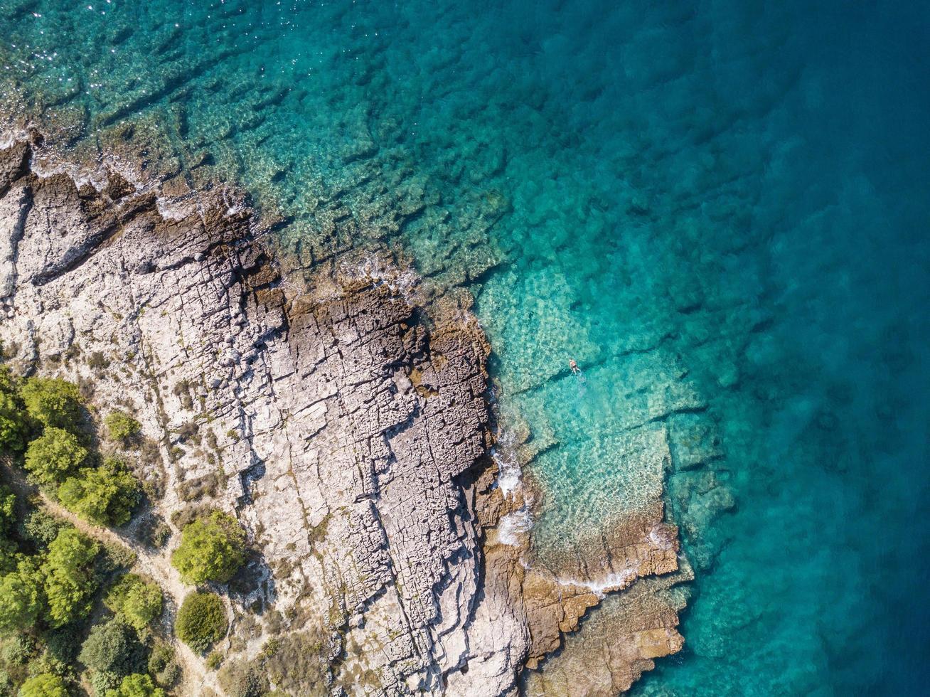 vista aerea dello snorkeler solista in acque turchesi costiere verdi foto