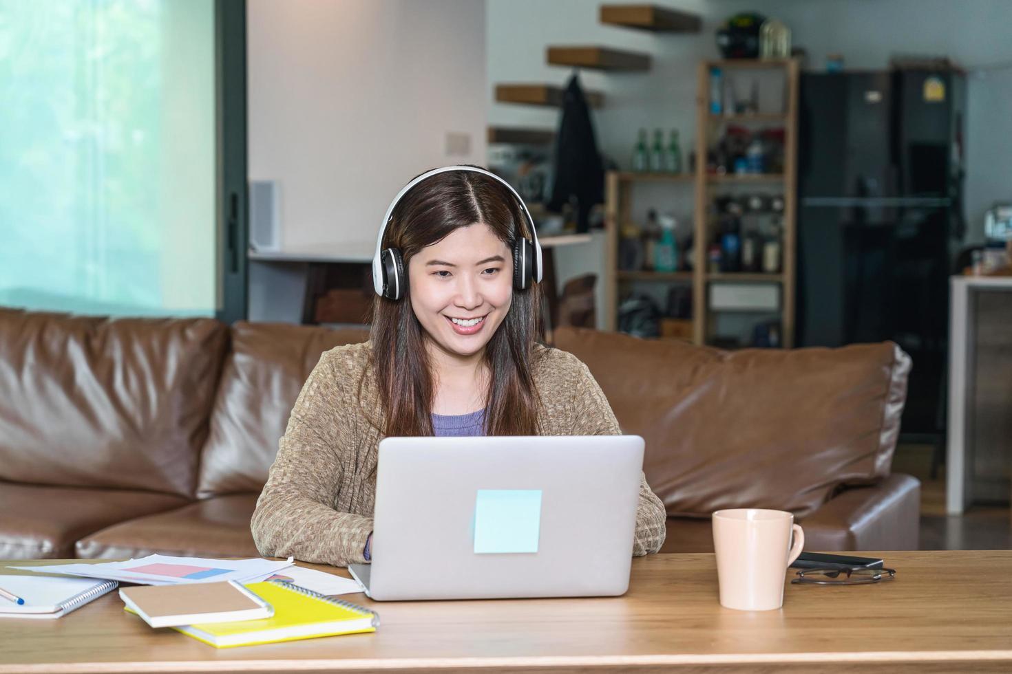 donna asiatica di affari che per mezzo del computer portatile di tecnologia a casa foto