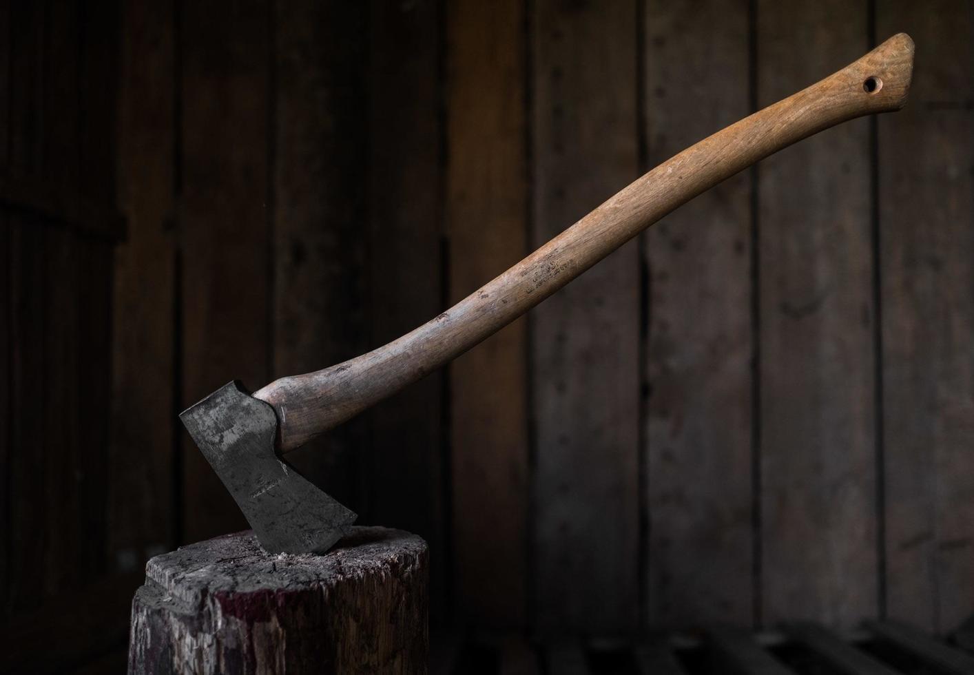 un'ascia di ferro bloccata in un tronco di legno foto