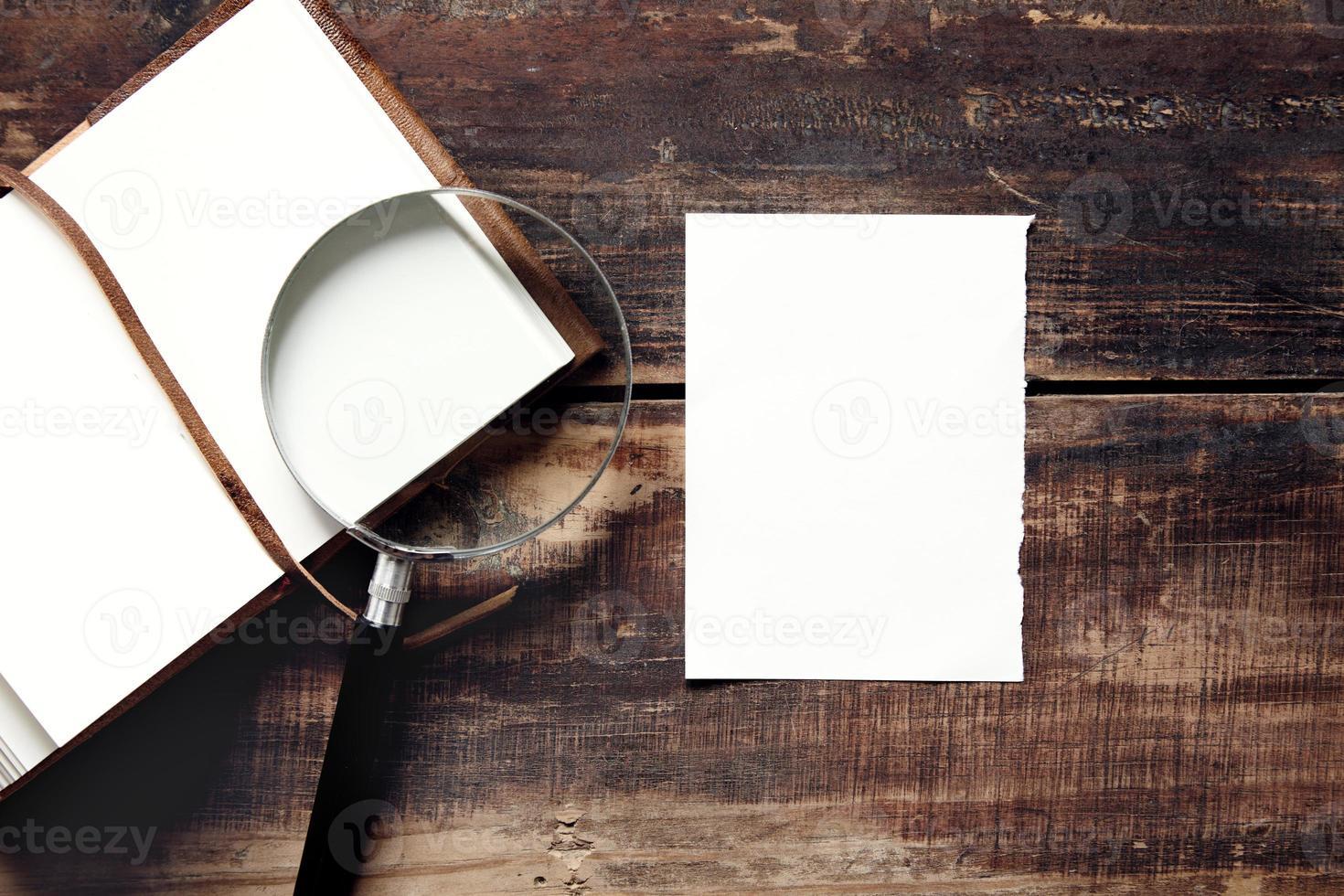 taccuino, foglio di carta e lente d'ingrandimento su un tavolo di legno foto