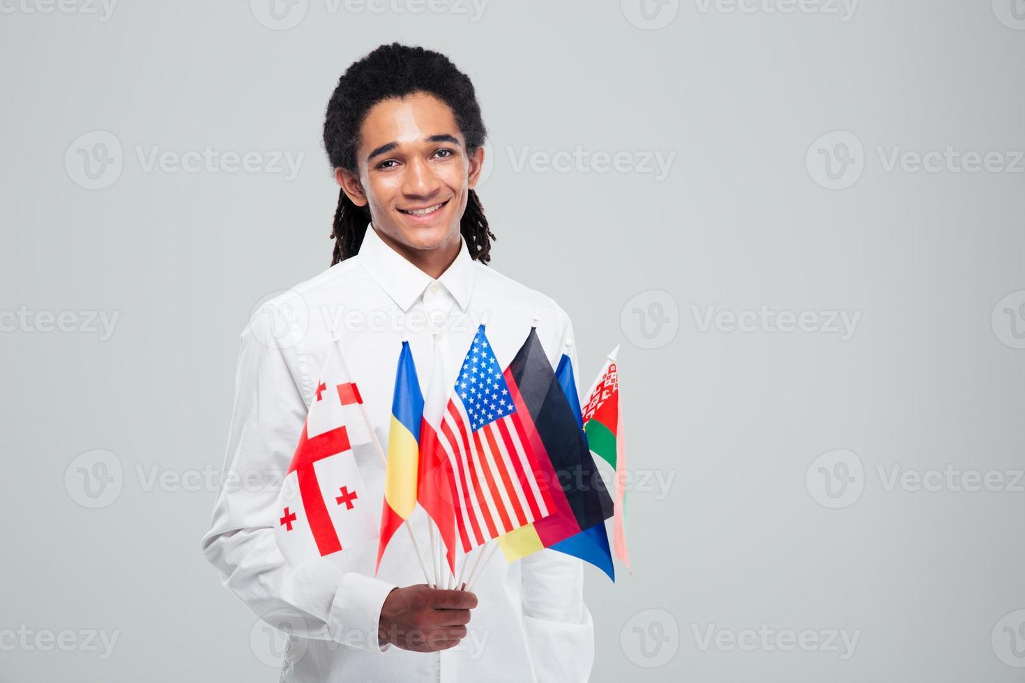 uomo d'affari afroamericano tenendo le bandiere del mondo foto