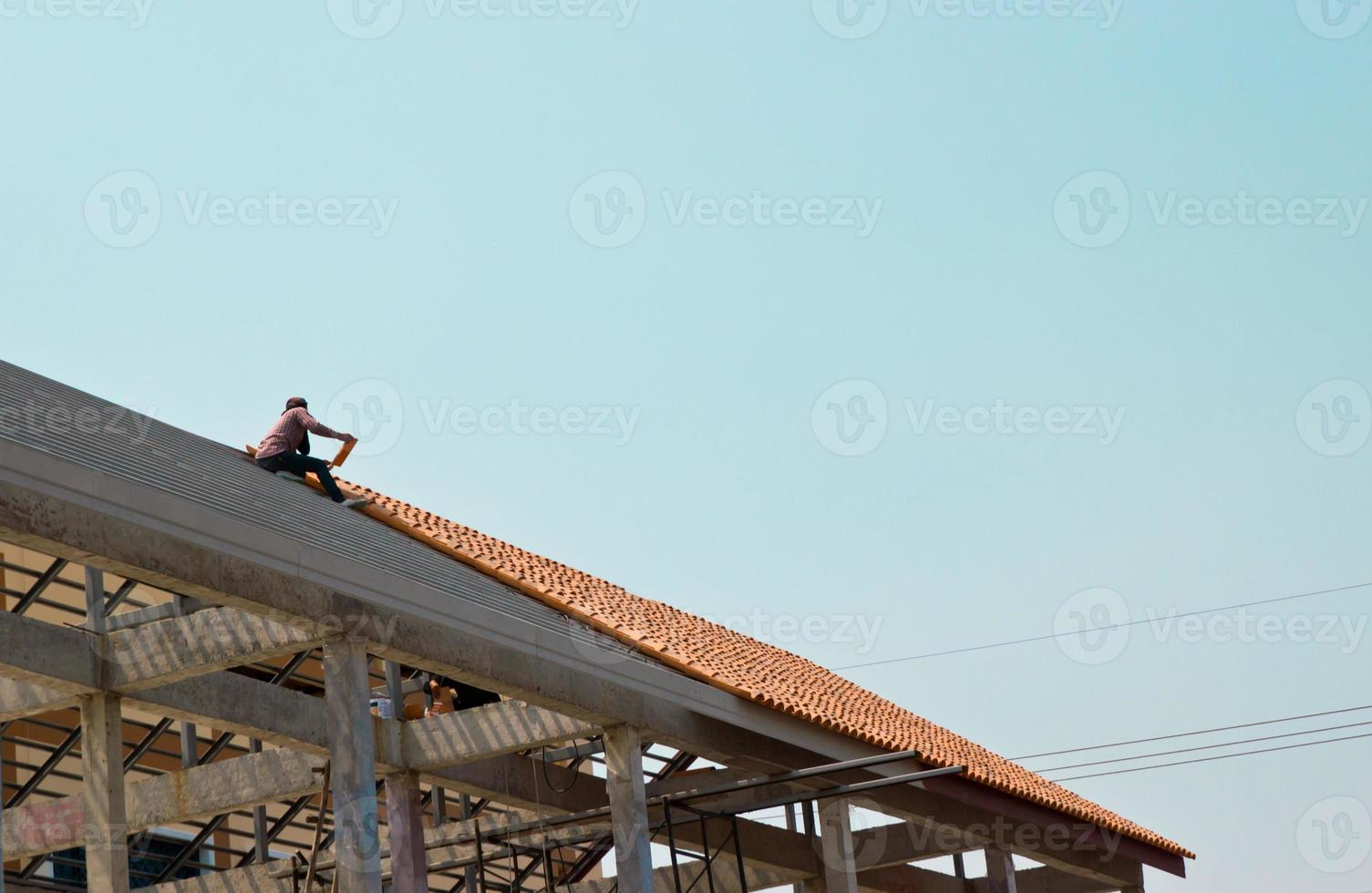 lavoratore sul tetto a lavori di avvitatura foto