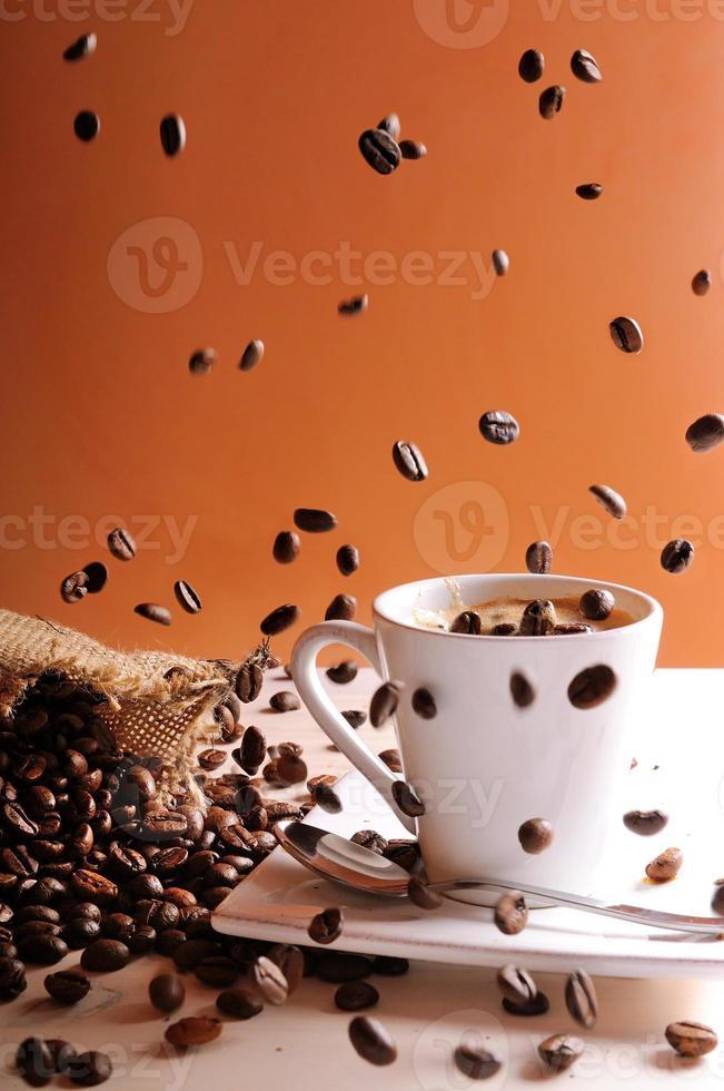 chicchi di caffè che cade sul tavolo con una tazza di caffè foto