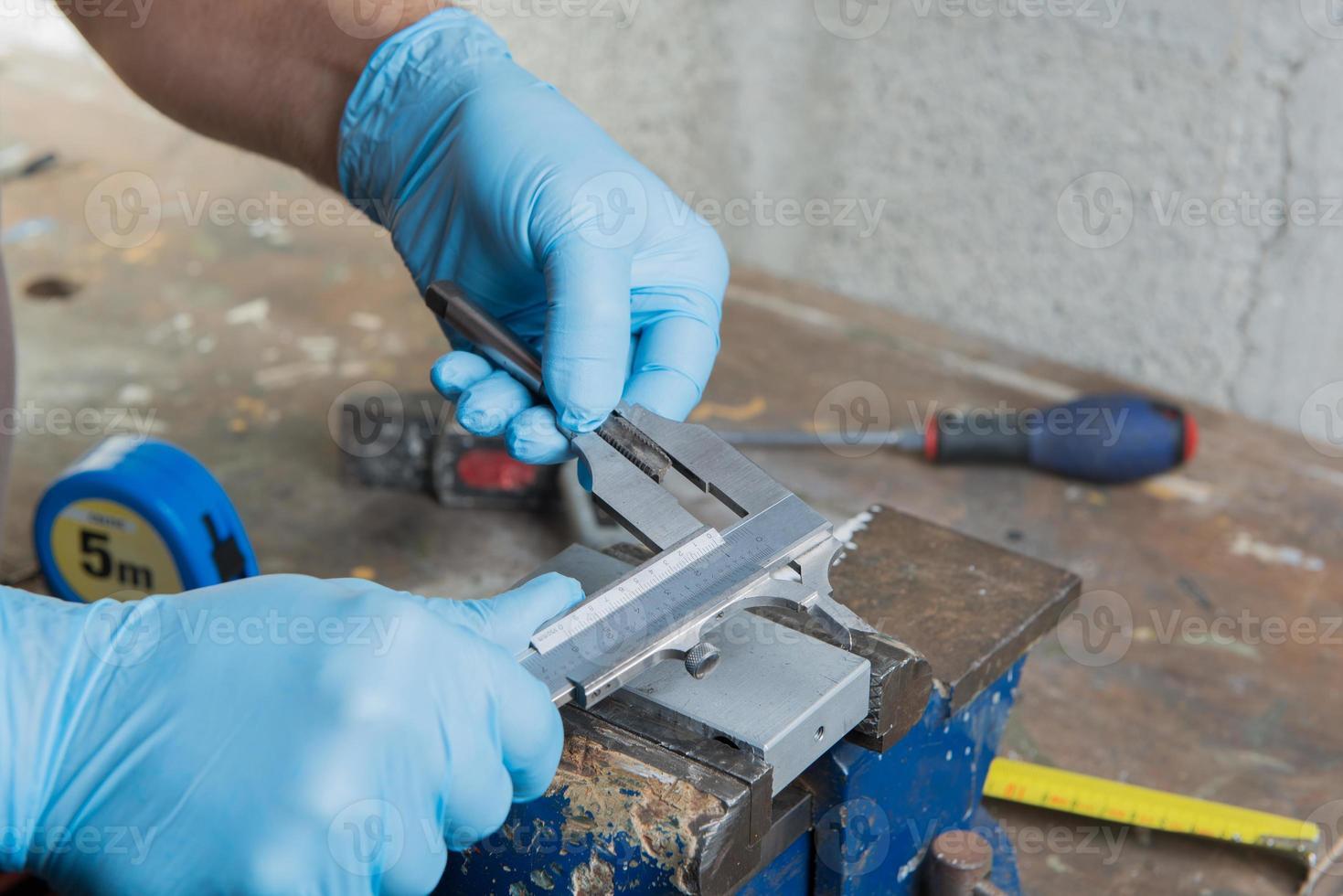 meccanico con guanti blu e un calibro a corsoio foto