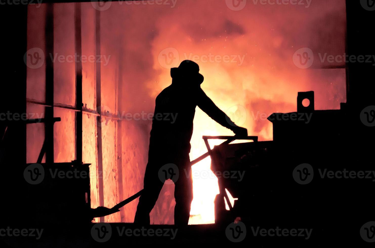 uomo che lavora nel ferro fuso che spruzza - immagine di riserva foto
