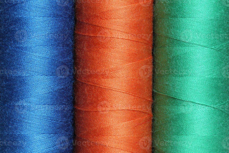 tre bobine di fili di poliestere colorati foto