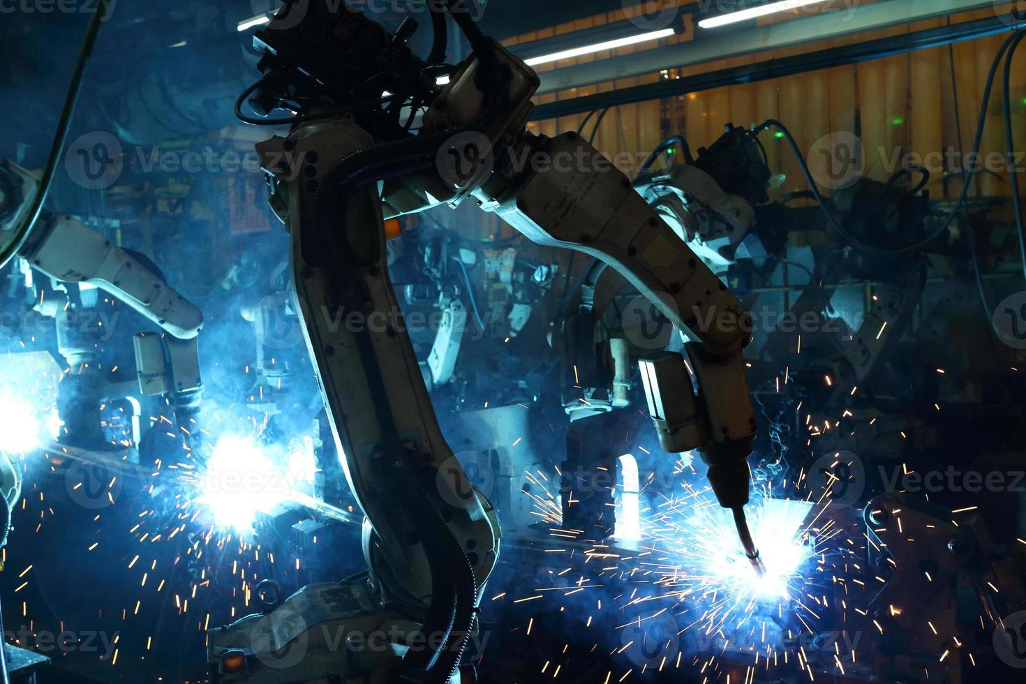 i robot di saldatura di gruppo stanno lavorando nel settore delle parti automobilistiche. foto