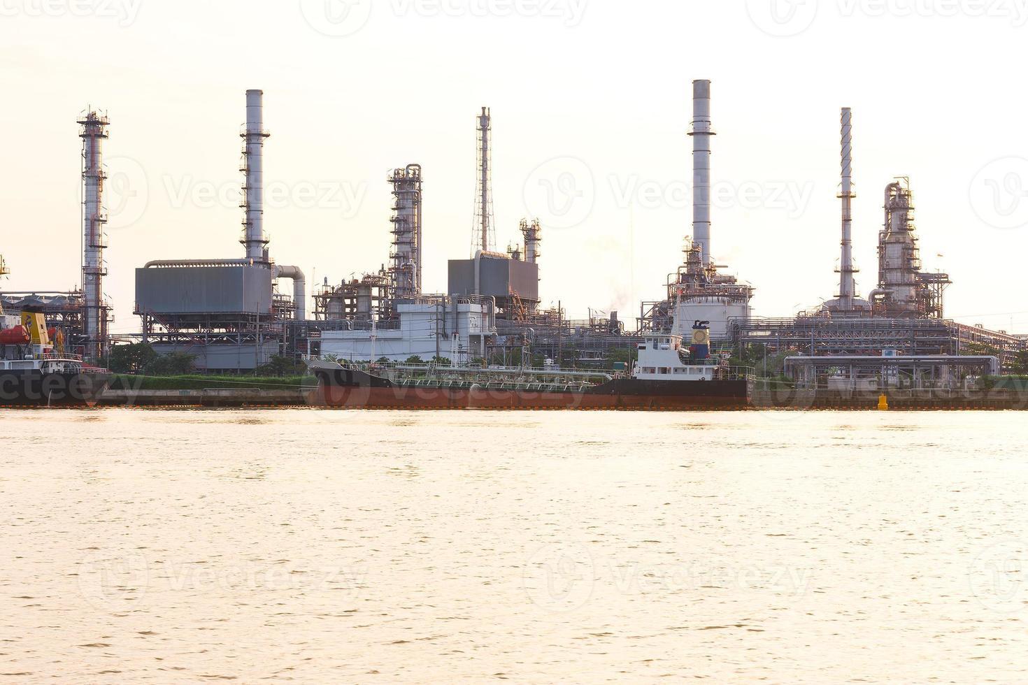 raffineria di petrolio con la nave da carico che parcheggia vicino al fiume foto