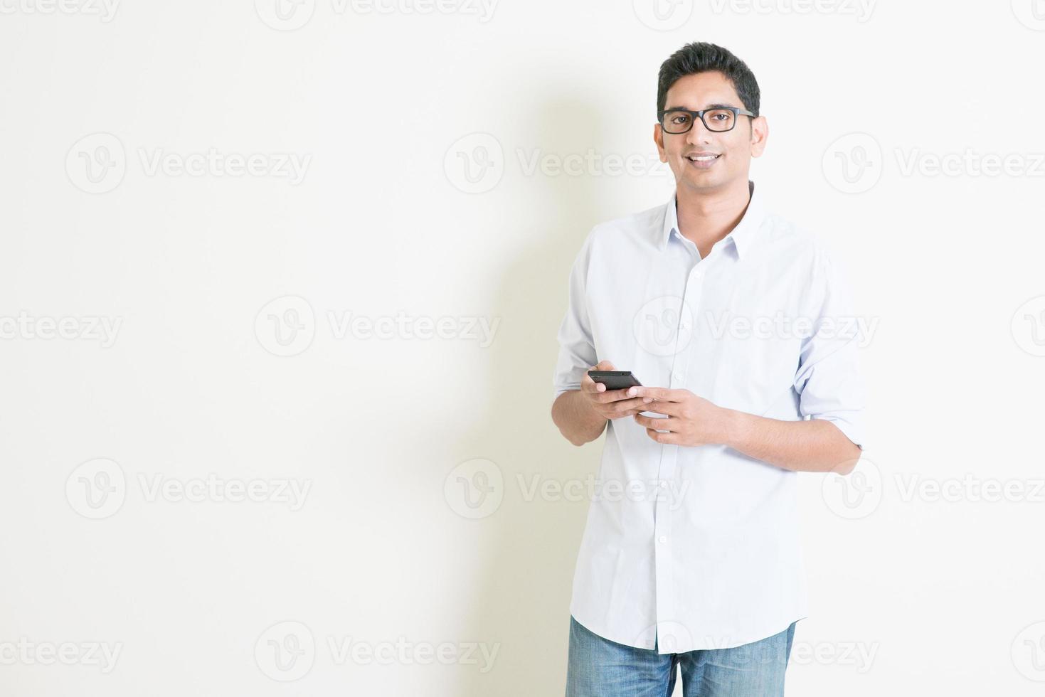 maschio indiano business casual utilizzando applicazioni mobili foto