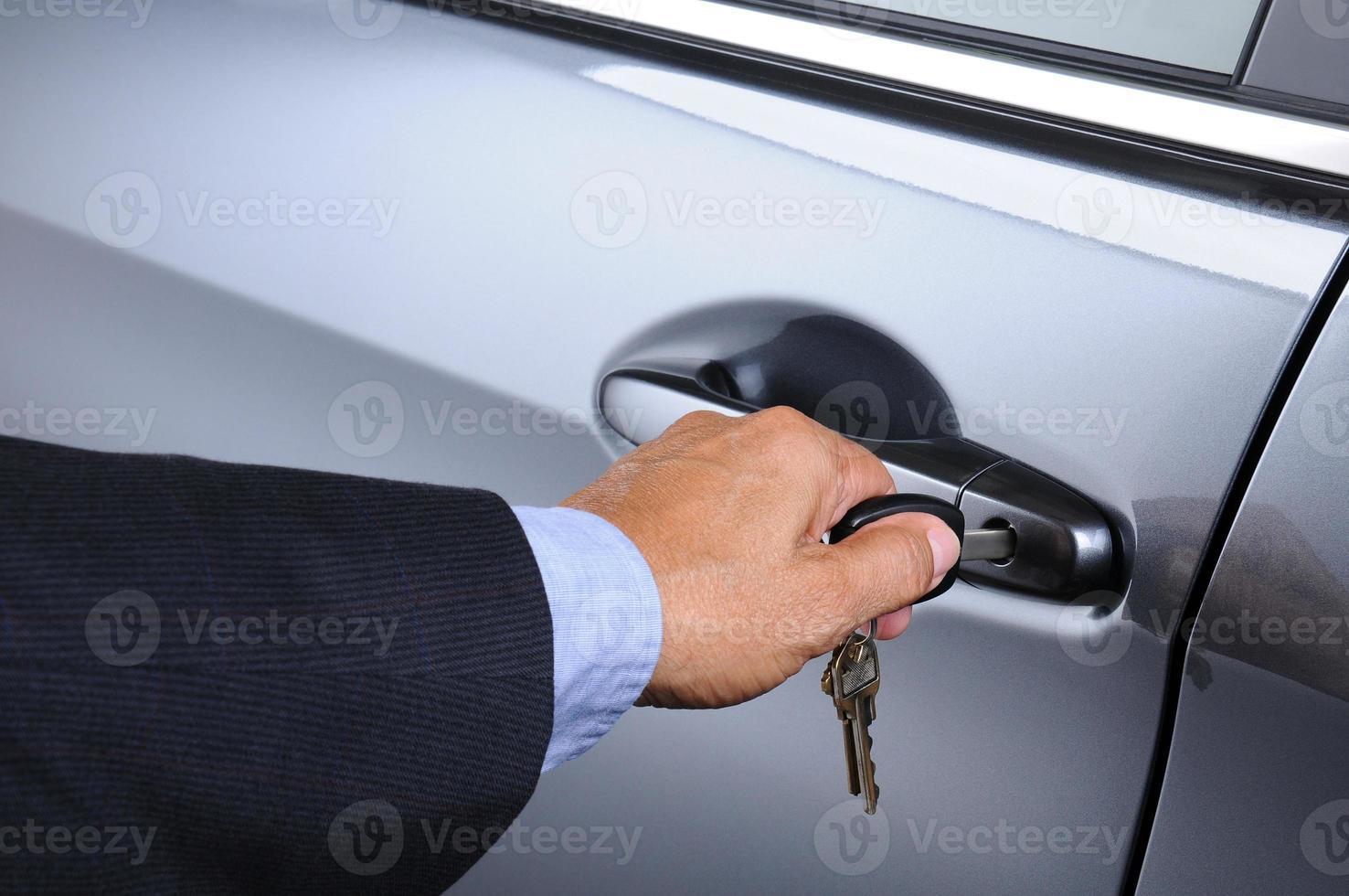uomo che mette la chiave della macchina nella serratura della porta foto