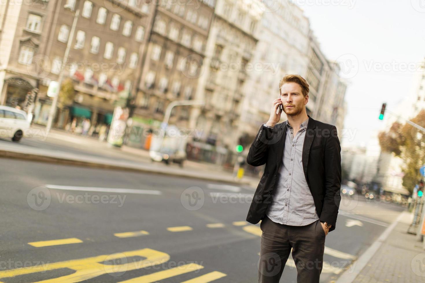 giovane uomo per strada con il cellulare foto