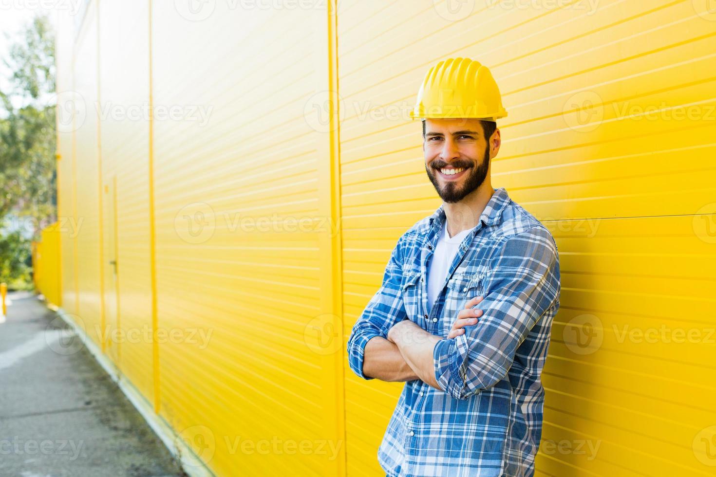 lavoratore adulto con casco sul muro giallo foto