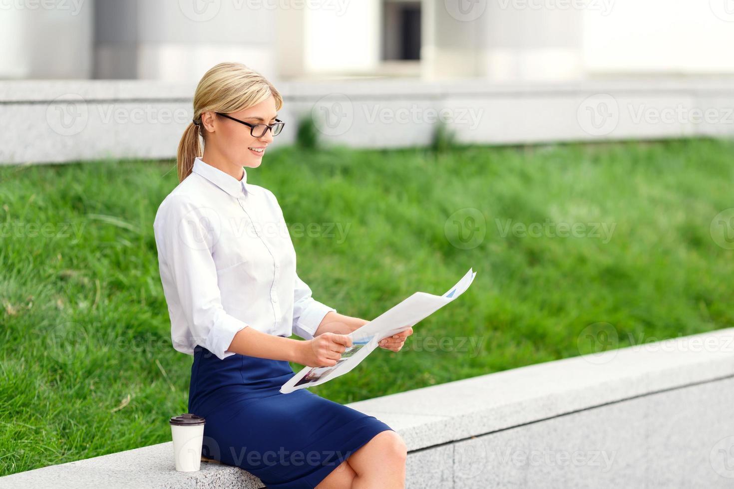 piacevole donna che legge il giornale foto