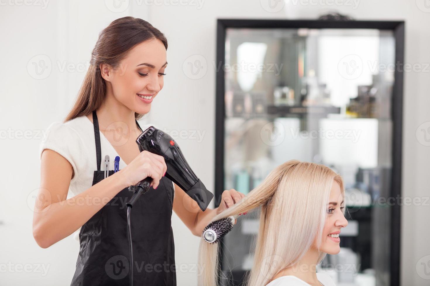 attraente parrucchiere femminile sta lavorando con gioia foto