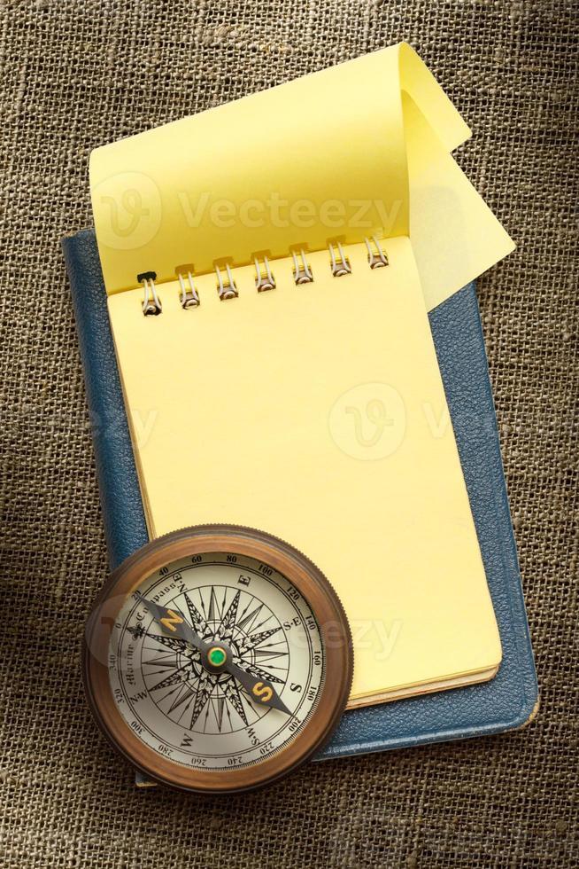 bussola vintage e blocco note giallo bianco foto