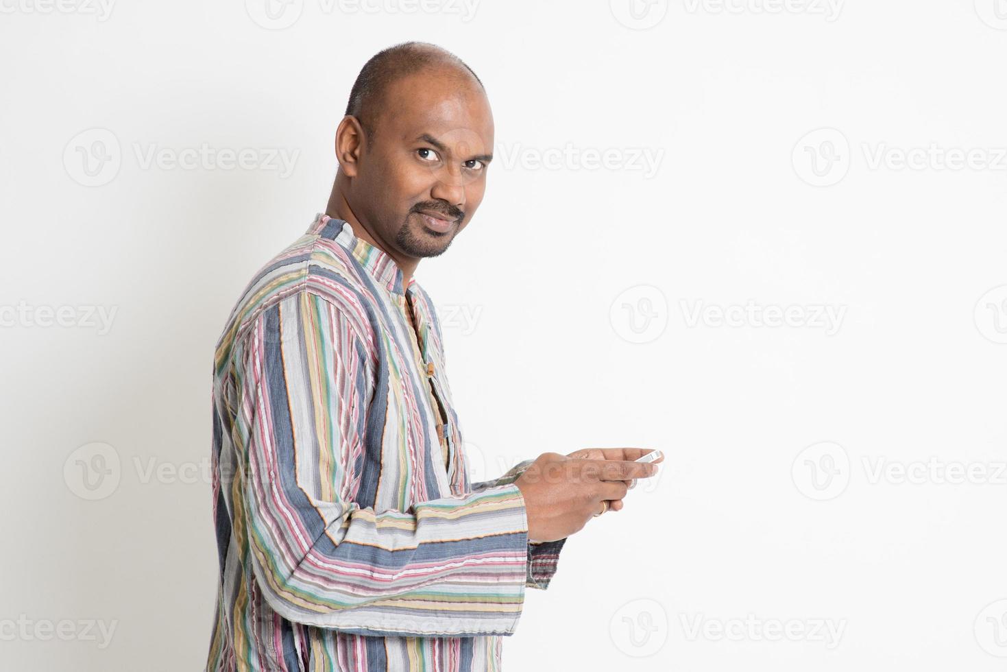 uomo indiano casuale maturo che gioca i giochi dello smartphone foto