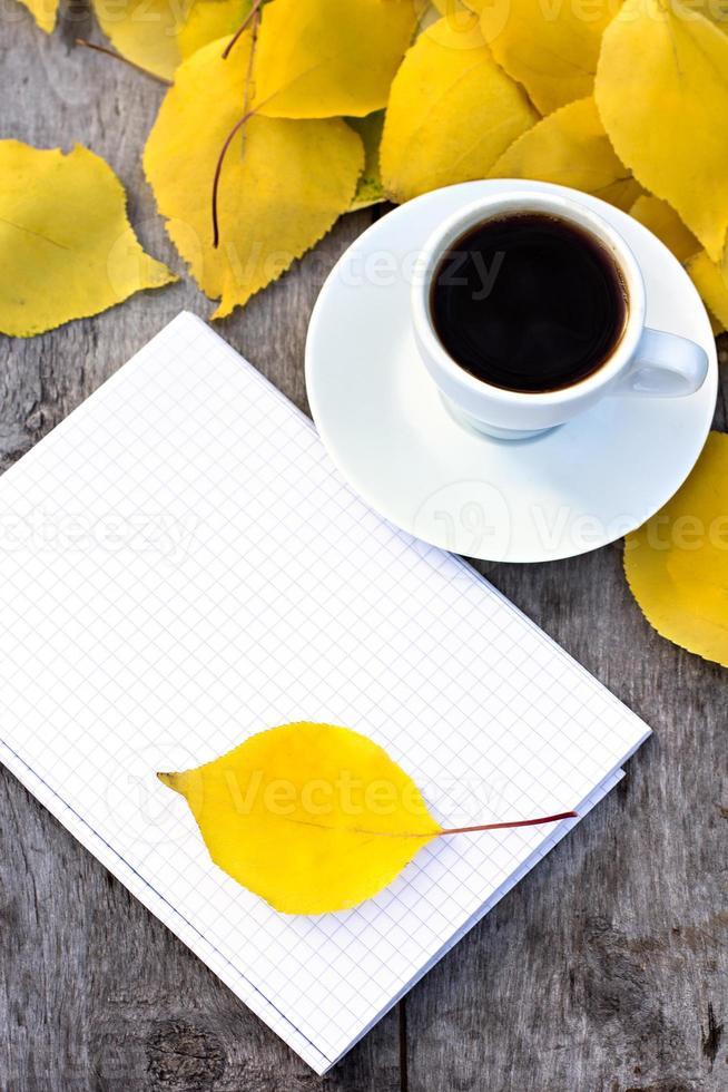 taccuino, tazza di caffè e foglie di autunno gialle foto