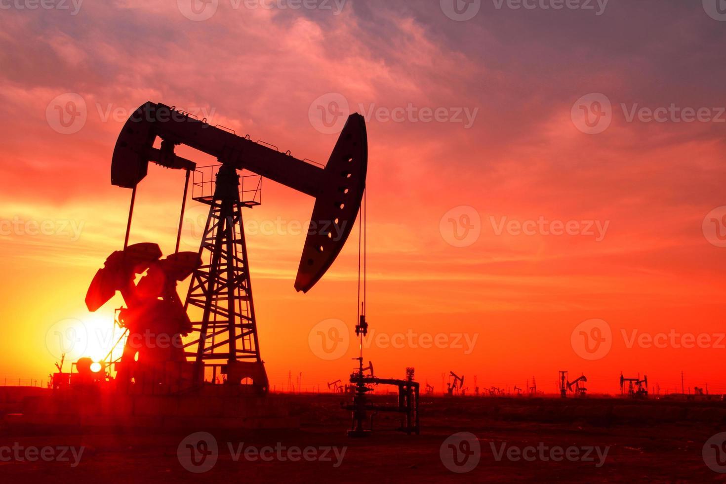 una silhouette di una pompa dell'olio in un campo petrolifero al tramonto foto