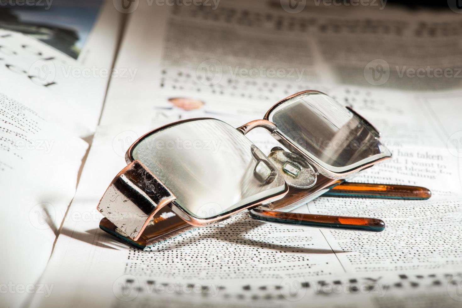 occhiali sul giornale foto