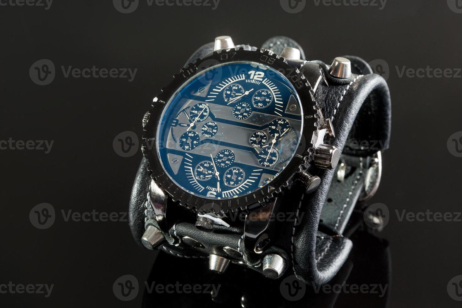 primo piano di orologio da polso su uno sfondo nero foto