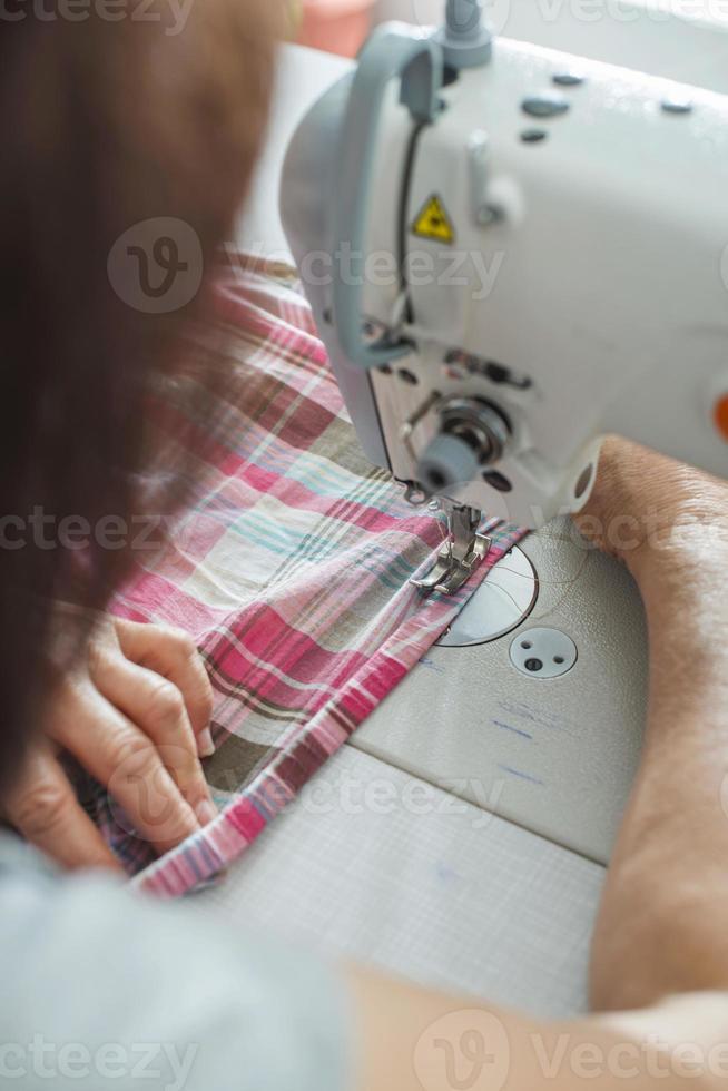 le donne cuciono sulla macchina per cucire foto