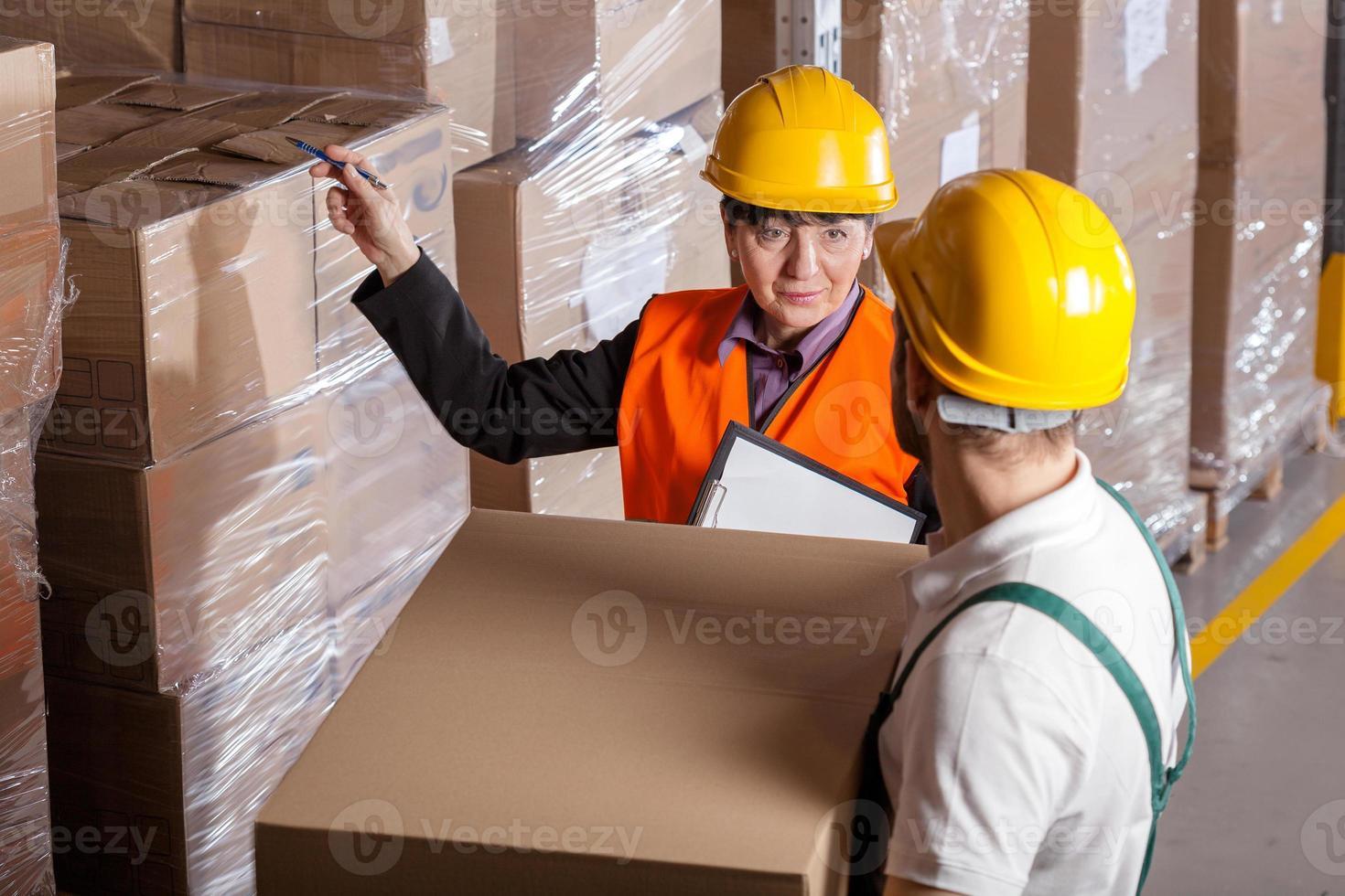 manager dando istruzioni al lavoratore in magazzino foto