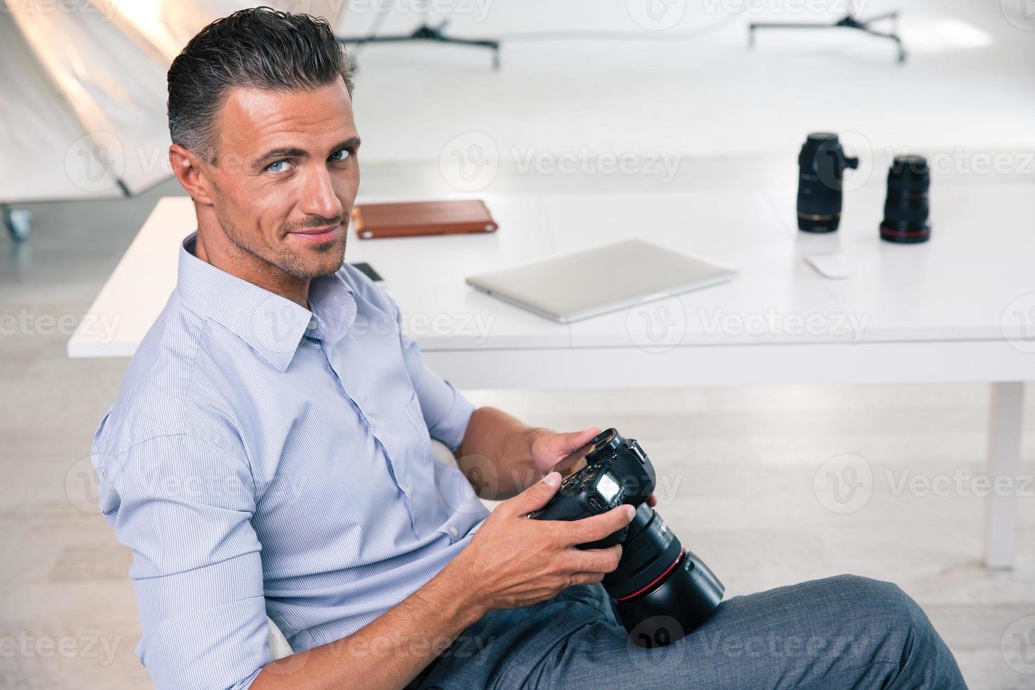 fotografo bello sorridente che usando macchina fotografica foto