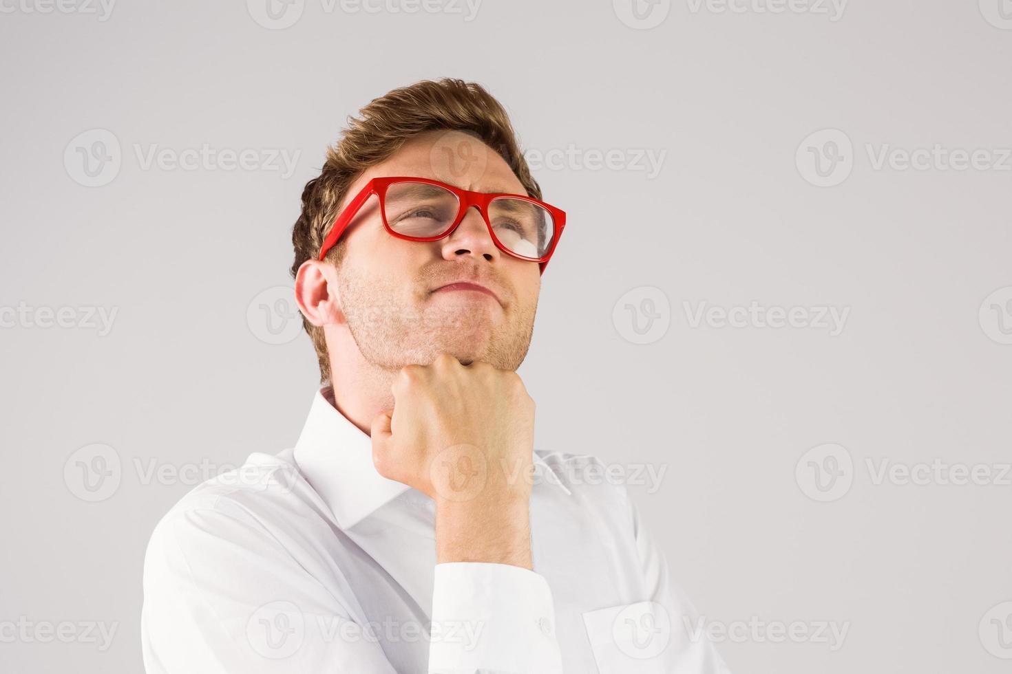 giovane imprenditore geek con la mano sul mento foto