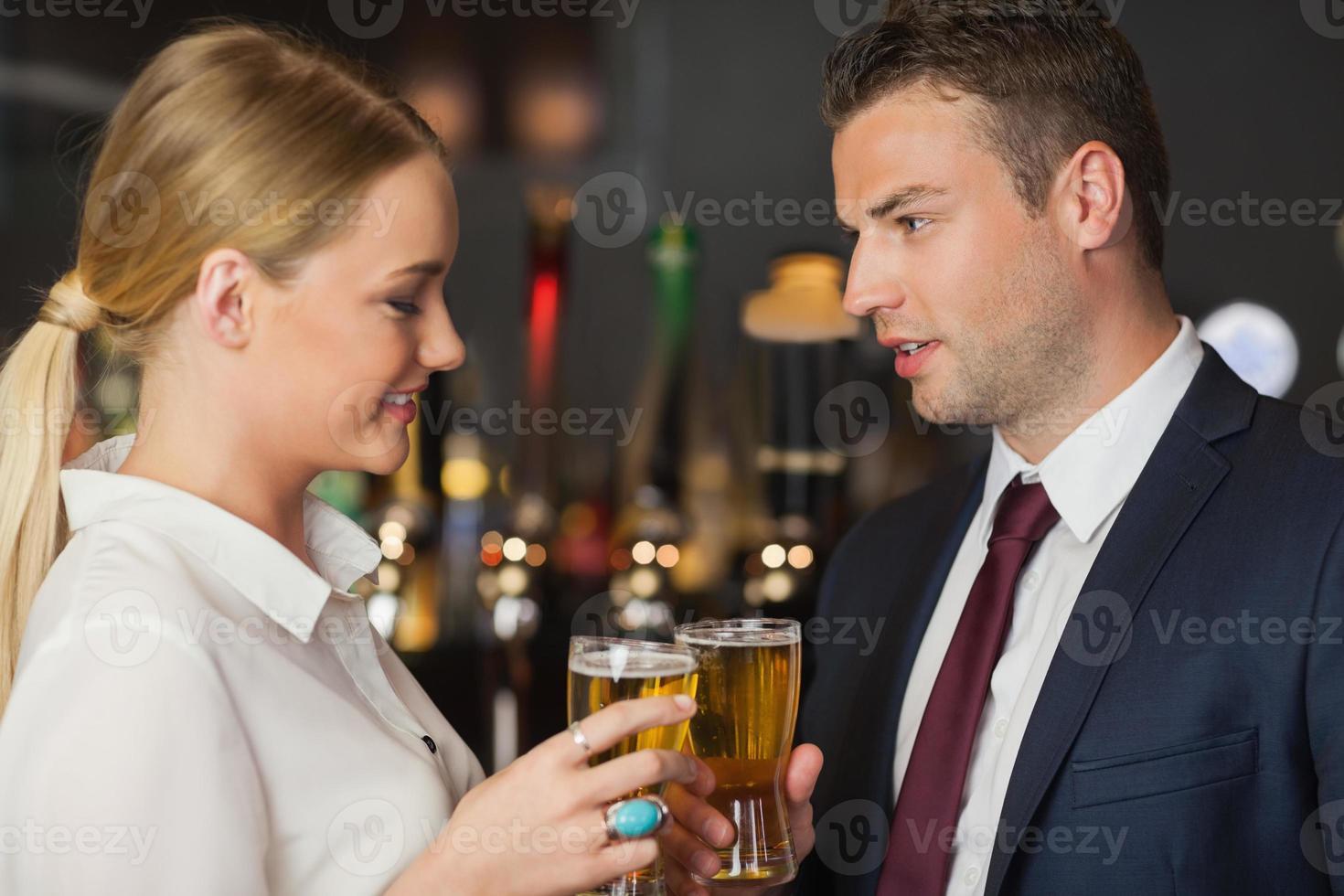 colleghi tintinnano i loro bicchieri di birra foto