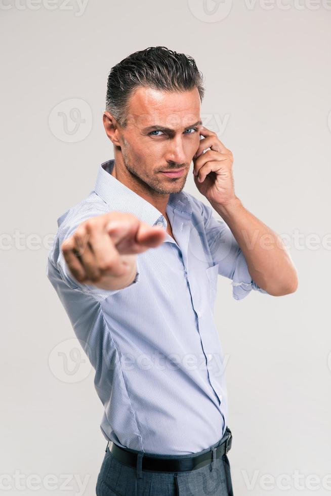 uomo d'affari parlando al telefono e indicando la fotocamera foto